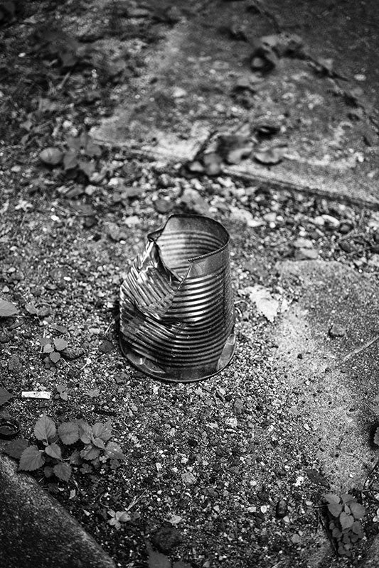 Black and white photograph of a dented tin can used to hold cigarette butts found