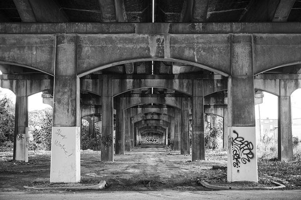 Black and white photograph under the 1st Avenue North bridge that parallels Sloss Furnaces near downtown Birmingham, Alabama.