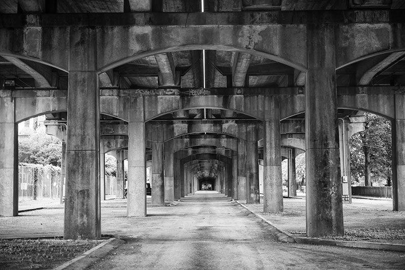 Black and white photograph under the 1st Avenue North bridge that runs near the Sloss Furnaces in an industrial area near downtown Birmingham, Alabama.