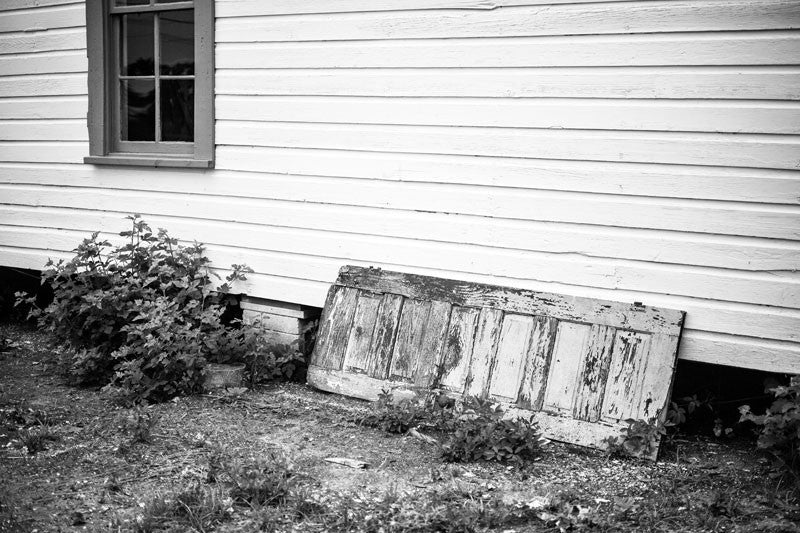 Black and white photograph of an old house with a peeling antique wooden door propped against an outside wall, in Birmingham, Alabama.