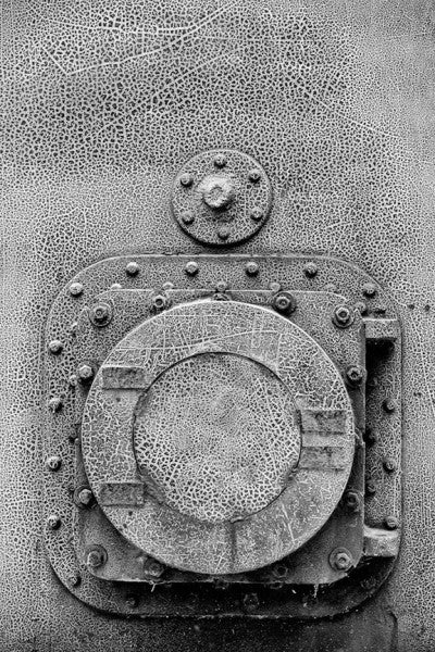 Black and white photograph of round door with cracked paint texture at Birmingham's historic Sloss Furnaces.