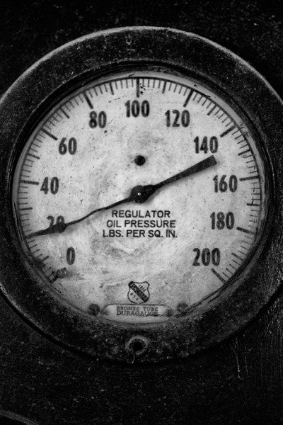 Black and white industrial photograph of an oil pressure gauge no longer in use at the old Sloss Furnaces in Birmingham, Alabama.
