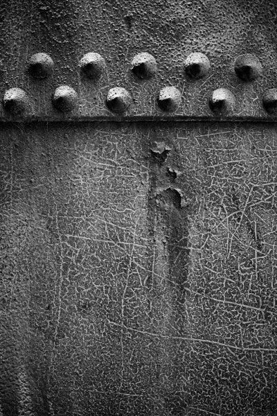 Black and white industrial photograph of big rivets on a textured pipe at Sloss Furnaces in Birmingham, Alabama.