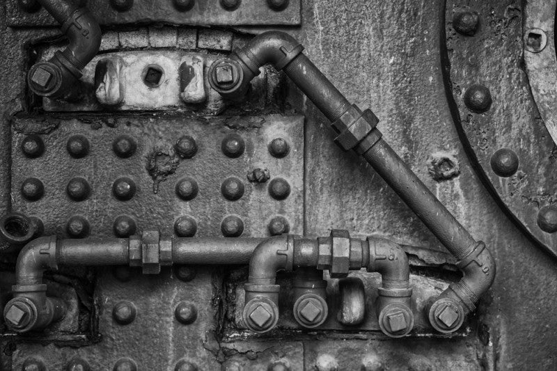 Black and white retro industrial photograph of pipes, rivets, and fittings.