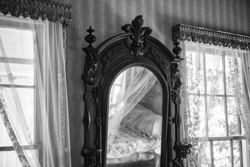 Black and white architectural interior photograph of an ornate wooden mirror inside a bedroom at Birmingham's historic Arlington House.