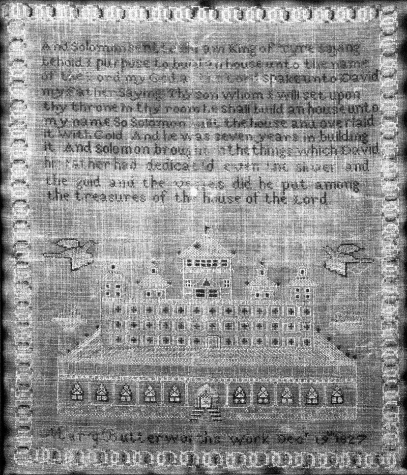 "Black and white photograph of a hand-stitched sampler completed in 1827 by Mary Butterworth, seen in Birmingham's historic Arlington House. The sampler features a Bible verse at top, and the bottom reads, ""Mary Butterworth's work Dec. 19th, 1827."""