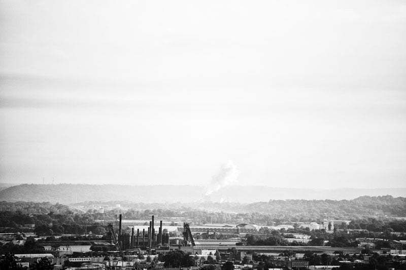 Black and white photograph of industrial Birmingham, Alabama in a long view, including the chimneys of Sloss Furnaces.