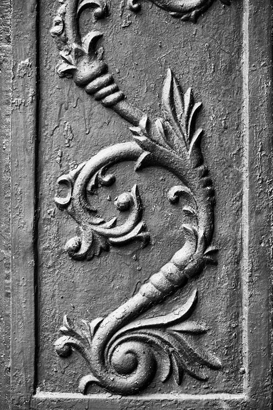 Black and white photograph of an antique cast iron flower architectural decoration, found on the exterior of an old storefront building in a small town.