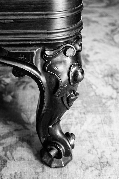 Black and white photograph of an ornate table leg standing on a threadbare rug inside a big old house.