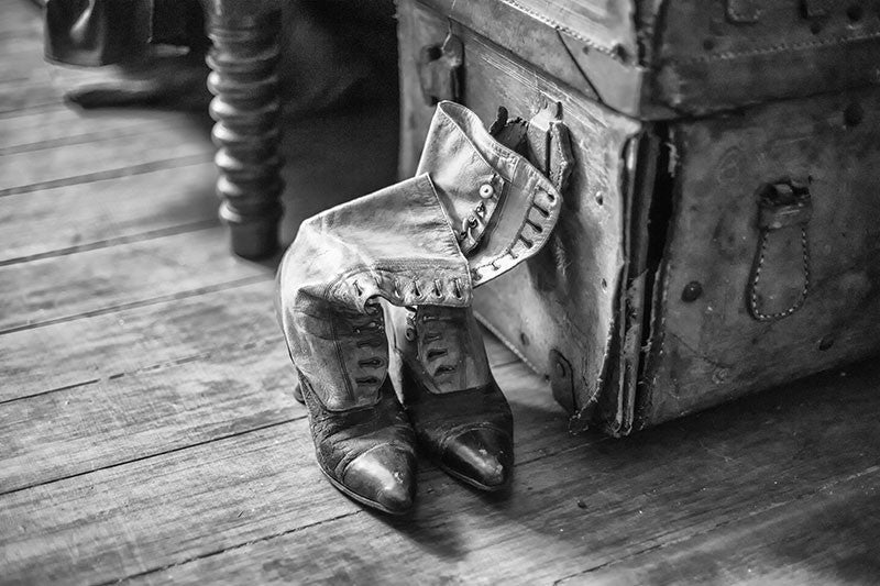 "Black and white photograph of a pair of old Victorian-era ""granny boots"" displayed beside a tattered leather trunk, found in the attic of an old house."