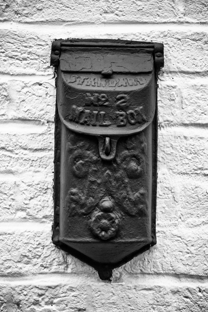 Black and white photograph of old-fashioned metal mailbox on the brick wall of a historic building in St. Charles, Missouri.