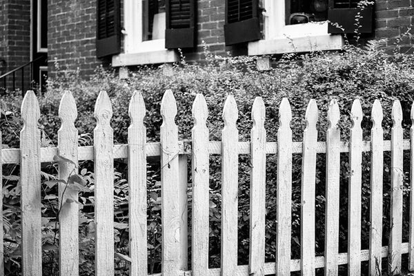 Black and white photograph of a white picket fence in the historic district of St. Charles, Missouri.