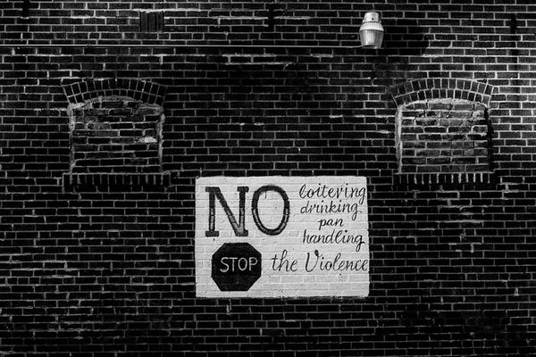 "Black and white photograph of a hand-painted sign on a brick wall in North St. Louis, Missouri. The text reads ""No loitering drinking panhandling. Stop the violence."""