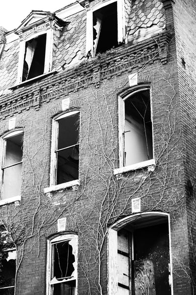 Black and white photograph of a beautiful old house in the College Hill neighborhood of St. Louis, now abandoned and in decline.