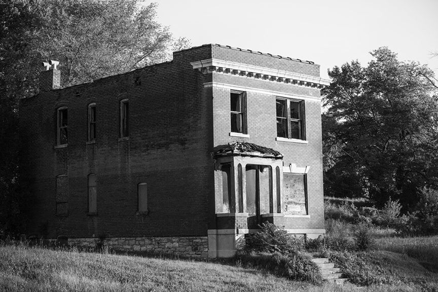 Black and white photograph of an abandoned historic row house in the College Hill neighborhood of St. Louis. Much of the neighborhood dates from the 1870s to the 1890s, and is now sporadically occupied, with many of these grand old structures left abandoned to decay.