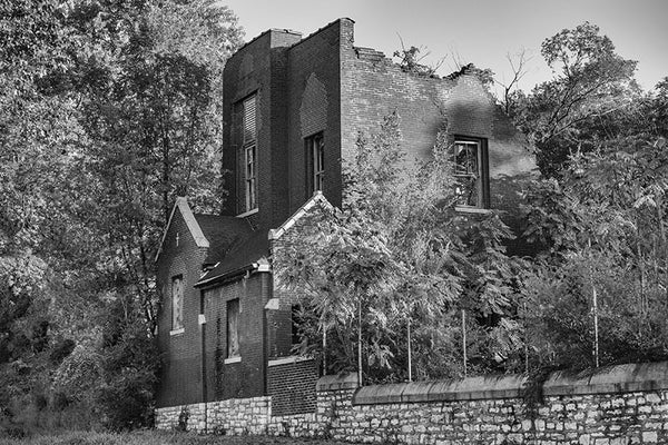 Black and white photograph of an abandoned, collapsing church on an overgrown lot in the College Hill neighborhood of St. Louis.