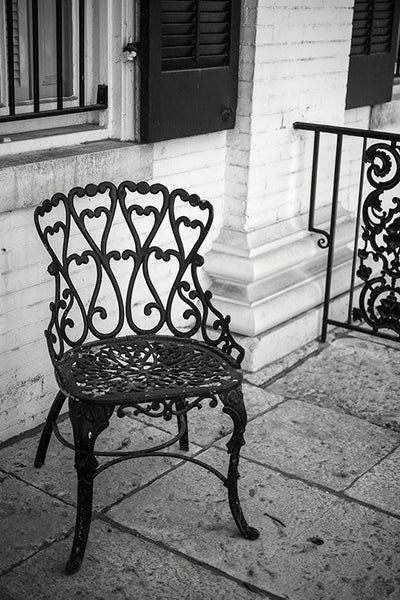 Black and white photograph of a chair on the front porch of the beautiful and historic Chantillon-DeMenil Mansion in St. Louis, Missouri.