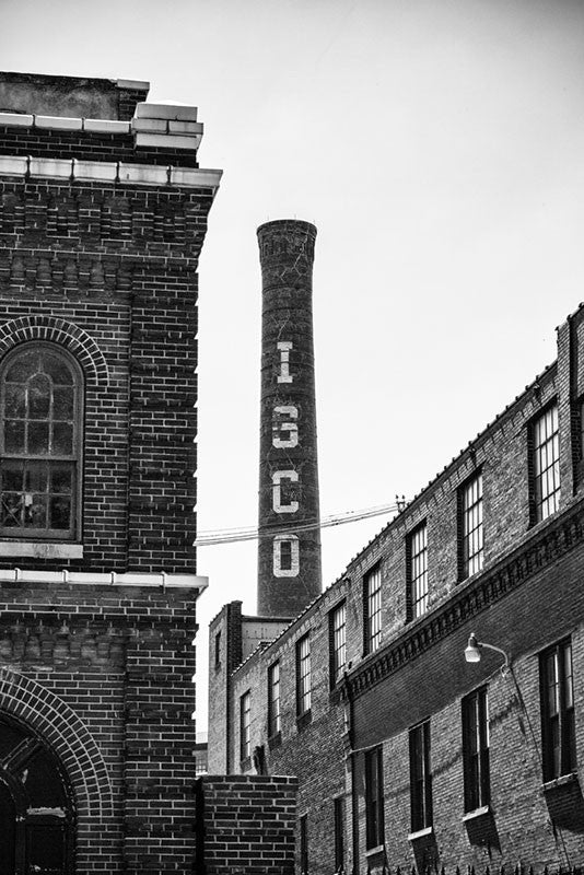 Black and white photograph of the old Lemp Brewery complex in St. Louis, Missouri. Once the 4th largest brewery in the US, construction on the complex began in 1865, and the brewery was sold due to financial and personal problems inside the Lemp family. At one point owned by ISCO, which left its name on the prominent brick chimney. The brewery complex was built over a natural cave system, with a cavern leading to the nearby Lemp Mansion.