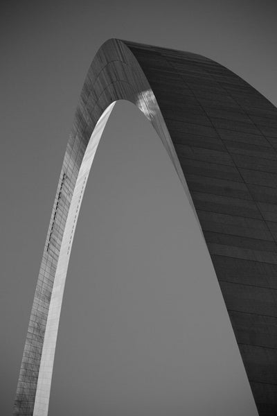 Black and white photograph of the famous St. Louis Gateway Arch, catching the final rays of the setting sun.