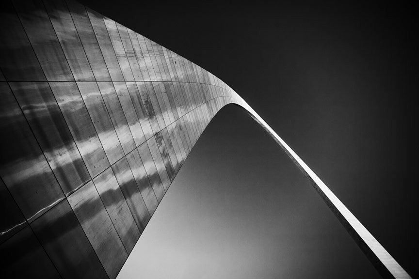 Black and white photograph of the famous St. Louis Gateway Arch against a dark sky, catching the last rays of light at sunset.