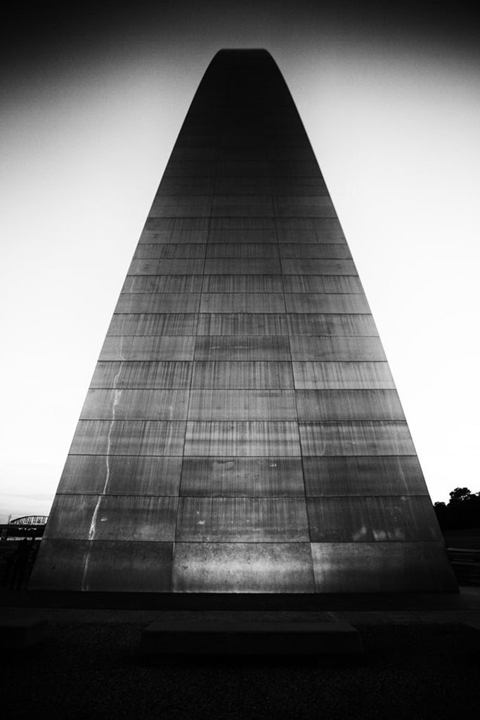 Black and white photograph of the famous St. Louis Gateway Arch at sunset, seen from the point of view of the base, looking up its steep metallic slope.
