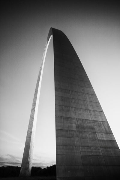 Black and white photograph of the famous St. Louis Gateway Arch catching the last rays of light at sunset.
