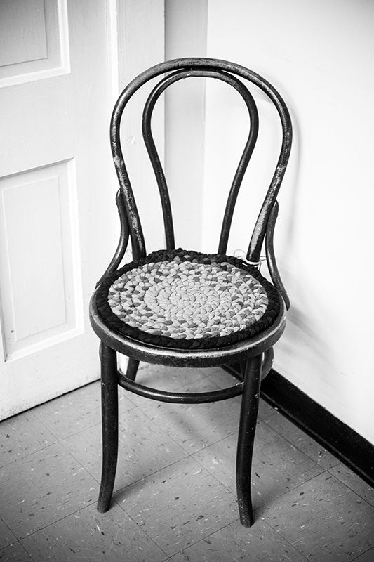 Black and white photograph of an antique chair with homemade cushion sitting in a corner in a big old house.
