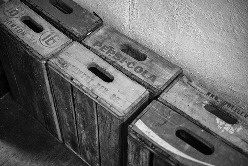 Black and white detail photo of vintage wooden soft drink crates stacked against the wall in an old house.