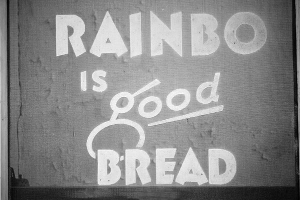 "Black and white photograph of a vintage ad for Rainbo Bread, as seen on a screen door. The ad reads, ""Rainbo is good bread."""