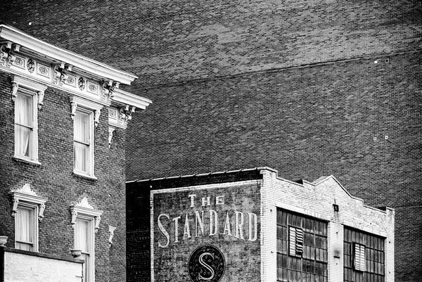 Black and white architectural photograph of brick buildings, including a vast brick wall, in downtown Nashville. The side of a smaller building displays a painted sign for The Standard.