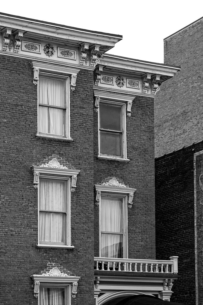 Black and white photograph of ornate wooden window ornaments and brick walls on historic buildings in Nashville, Tennessee.