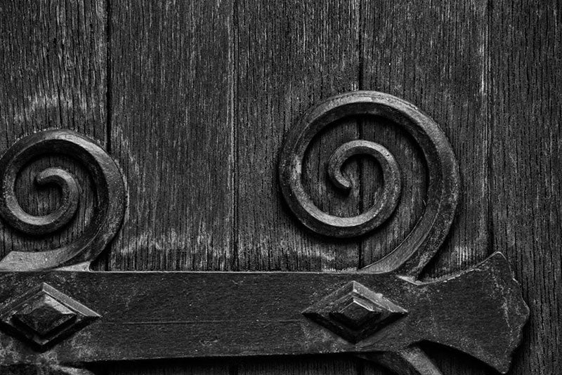 Black and white architectural detail photograph of the large wooden door on the exterior of the historic Christ Church in Nashville, Tennessee.