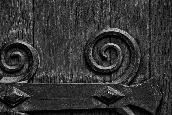 43f9aa92 Black and white architectural detail photograph of the large wooden door on  the exterior of the