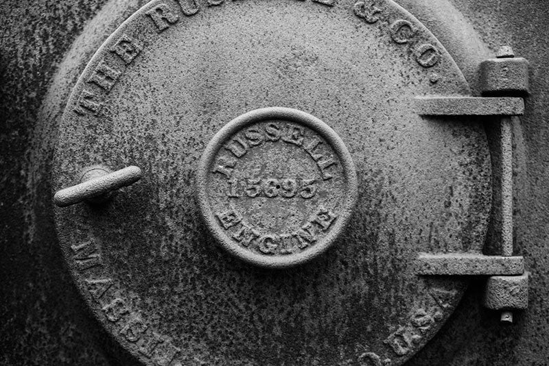 Black and white photograph of a rusty antique machine door marked by the Russell Engine Company.