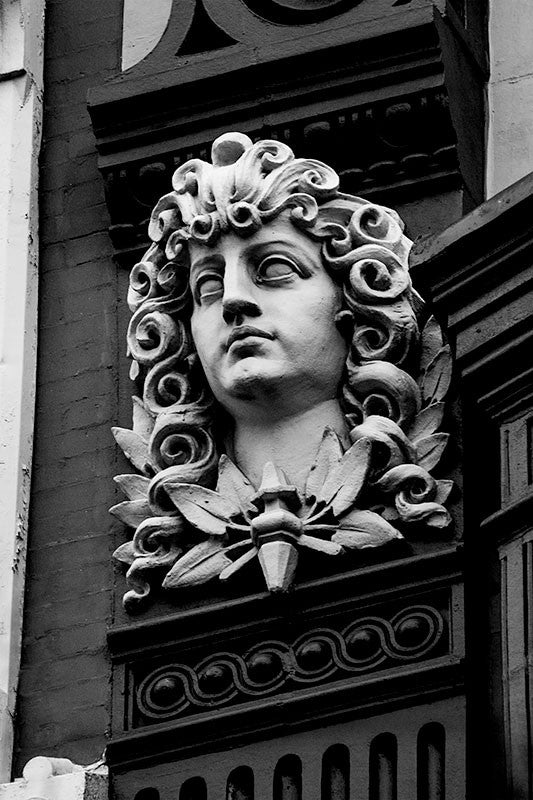 Black and white architectural detail photograph of classically-inspired, statue of a young man with curls in his long hair, on a building in downtown Philadelphia.
