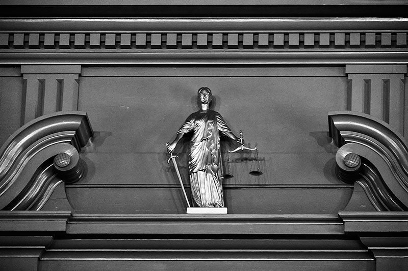 "Black and white photograph of a small, golden ""Justice is Blind"" statue on the interior of Independence Hall in Philadelphia."