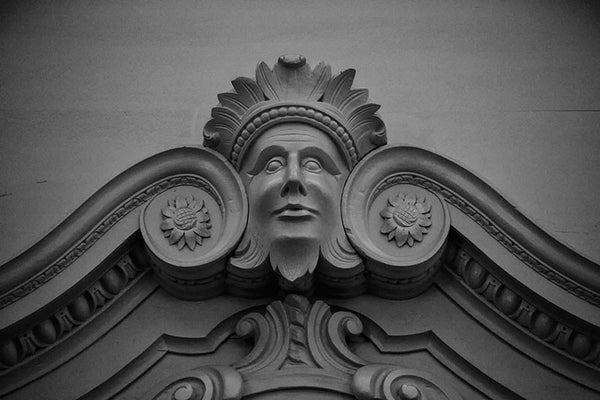 Black and white photograph of a carved wooden face on the interior woodwork of Independence Hall in Philadelphia.