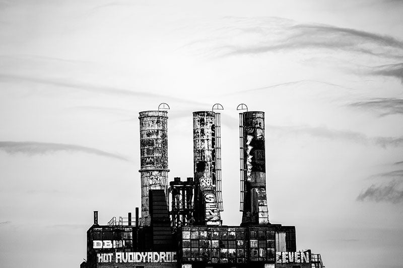 Black and white photograph of the three tall smoke stacks of the old Philadelphia Power Plant, seen from a distance.