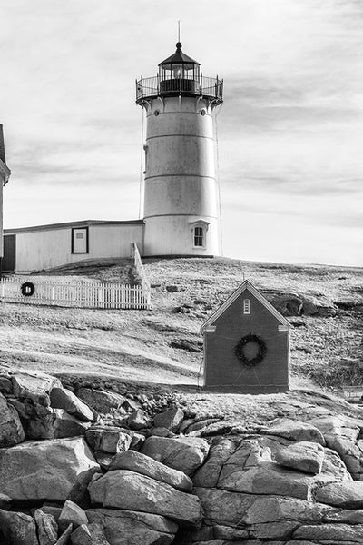 Black and white photograph of the beautiful Nubble lighthouse, which sits on a tiny island just yards off the coast at York, Maine. The lighthouse, officially called the Cape Neddick Lighthouse, began service in 1879 and is still in operation today. The lighthouse sits 88 feet above sea level atop the rocky Nubble islet.