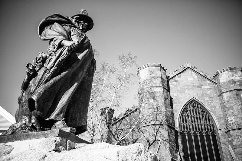 Black and white photograph of the statue of Roger Conant, pilgrim founder of Salem, positioned outside the Salem Witch Museum.