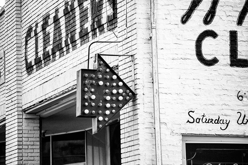 Black and white architectural detail photograph of a red arrow sign on a dry cleaning business