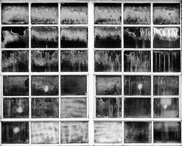 Black and white photograph of a grid of industrial windows with myriad textures, splashes, stains and tones. Each pane of glass looks like an individual work of art.
