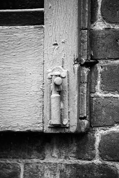 Black and white architectural detail photograph of an antique wooden shutter with cracking paint on an old house in historic Franklin, Tennessee.