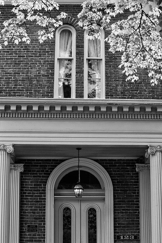Black and white photograph of the front of a historic Greek Revival house with Ionic columns in Franklin, Tennessee.