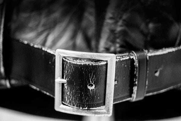 Black and white fine art photograph of a the silver buckle on a black leather jacket once owned and worn by Elvis Presley, seen in a museum exhibit.