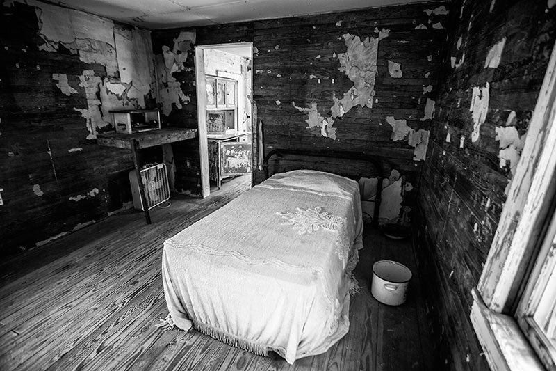 Black and white photograph inside the bedroom of the late blues musician Sleepy John Estes. Here we see his bed, covered by a bedspread, siting on bare wood floors and surrounded by wooden walls with small scraps of remaining original wallpaper. Estes small house in Brownsville, Tennessee has been preserved and relocated to a visitors center near the schoolhouse of Tina Turner, who also came from Brownsville.