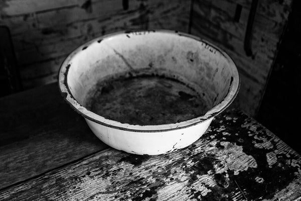 Black and white photograph of a wash basin on a table inside the home of the late blues musician Sleepy John Estes in Brownsville, Tennessee. The small shack where Estes lived has been preserved and relocated to a visitors center near the schoolhouse of Tina Turner, who also hails from Brownsville.