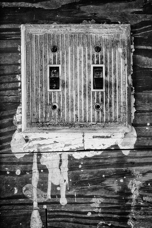 Black and white photograph of a grimy, old light switch plate surrounded by drips of white paint, inside the home of the late blues musician Sleepy John Estes in Brownsville, Tennessee.