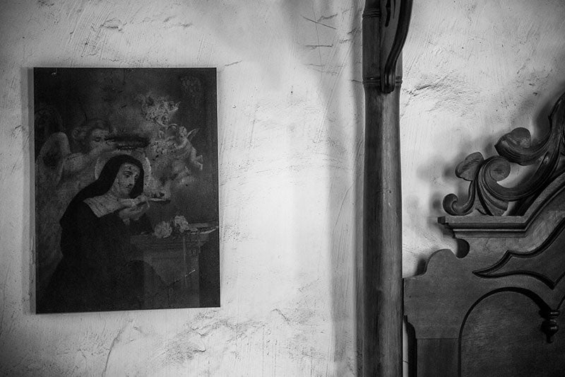 Black and white photograph of an antique portrait of The Madonna in Nun's habit hanging on a wall near the post of a wooden bed inside an old house in Lafayette, Louisiana.