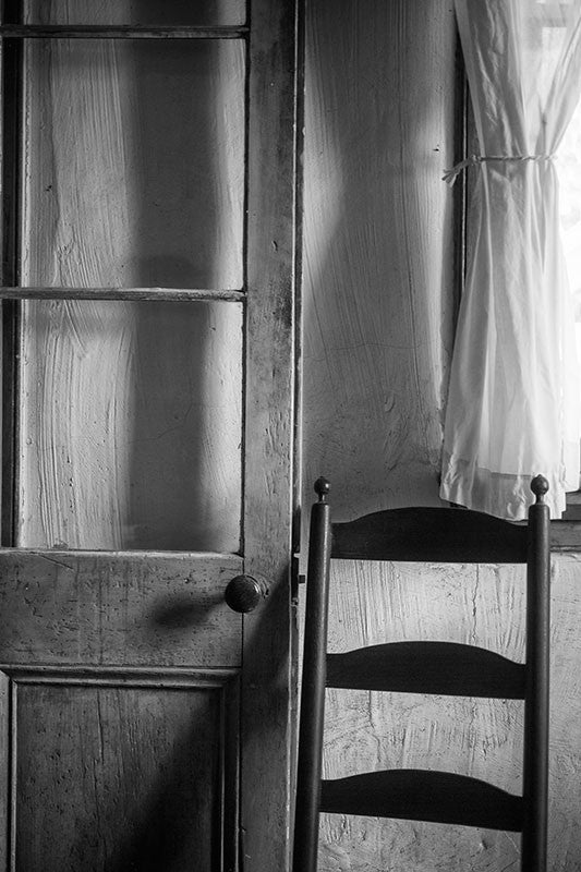 Black and white photograph of the inside of an old Cajun house in Lafayette Louisiana, with a French-style door, a simple wooden chair, and a sheer curtain.